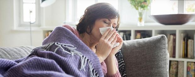 Frau liegt krank auf dem Sofa